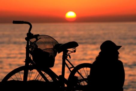 bicyclist rests on Mediterranean beach