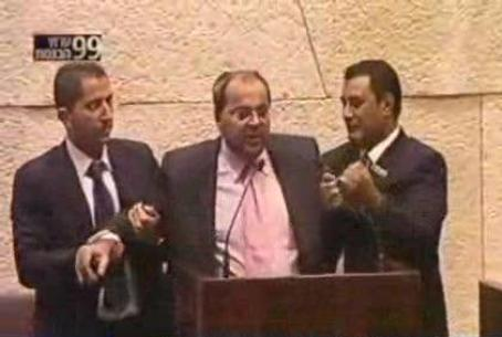 Arab MK Tibi Forcibly Removed from Podium