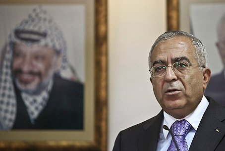 Fayyad in front of Picture of Arafat on wall