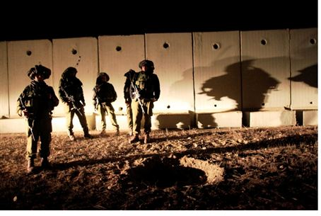 IDF troops view crater created by shell