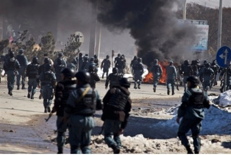 Afghan policemen march towards protesters