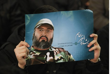 Hezboll supporter holds a poster of Mughniyeh