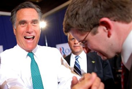 Romney greets audience during a campaign sto