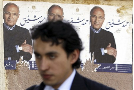 Man walks past campaign posters for Ahmed Sha