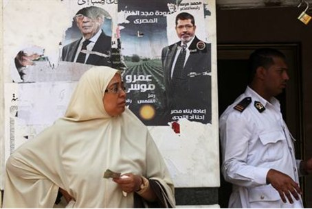 An Egyptian woman stands in front of posters
