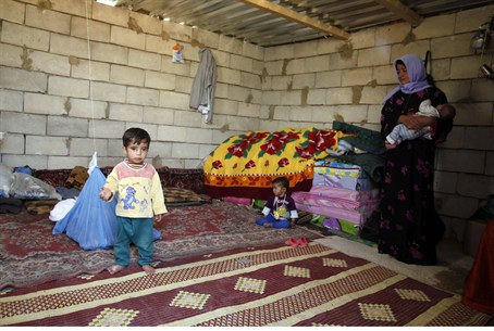 Syrian refugees sit in a temporary home in Le
