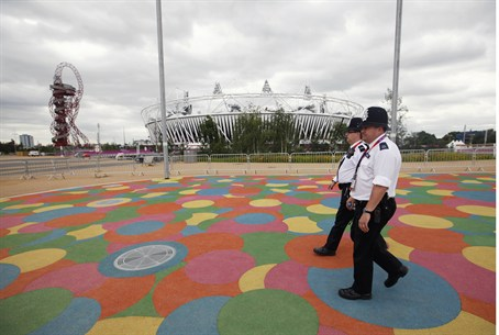 Police officers walk past the Olympic Stadium