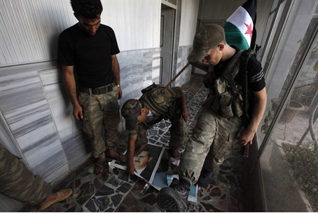 Free Syrian Army soldiers step on portraits o
