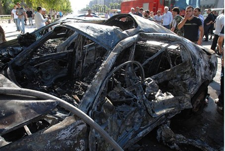 Syrians inspect the site of a car bomb blast