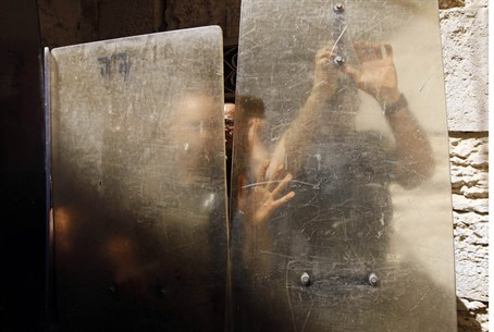 Police hold shields against rock-throwing Ara
