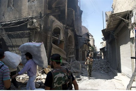 Syrian civilians walk past the rubble of buil