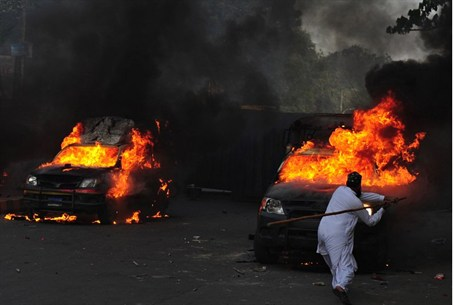 A Pakistani Muslim demonstrator hits a burnin