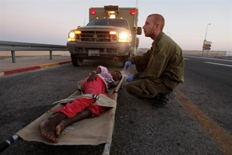 An Israeli soldier gives medical treatment to