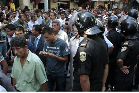 Tunisians walk past riot police