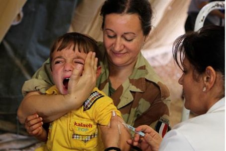 A Syrian boy cries as he gets an inoculation