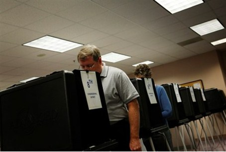 Voters cast ballots on touch-screen voting m