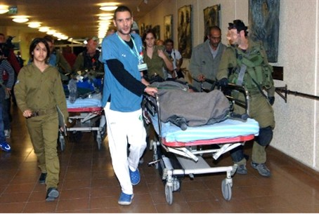 Wounded Israeli soldiers are wheeled into So
