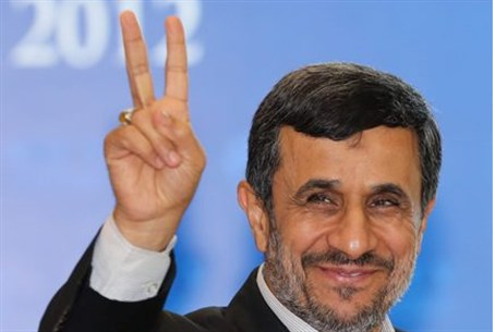 Ahmadinejad gives a sign to photographers in