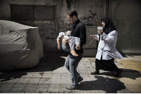 A Syrian man carries his wounded daughter in