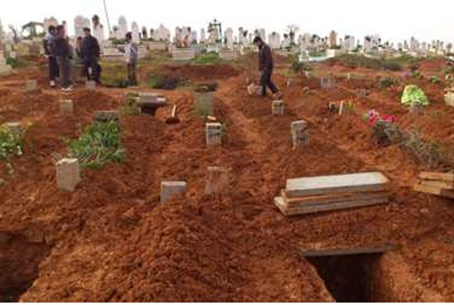Syrian residents look at fresh graves