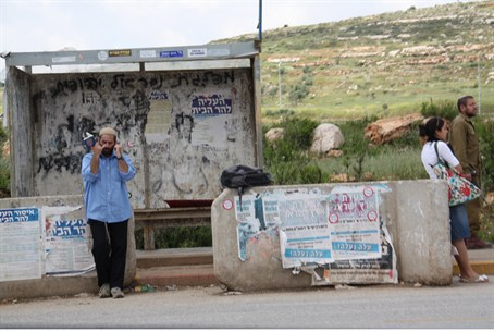 Israeli hitchhiker waits for a ride in Samari