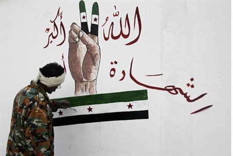 A member of the Free Syrian Army paints on th