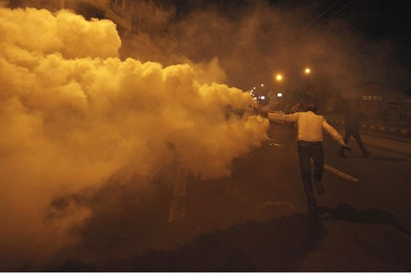 Anti-Morsi protester throws a tear gas canist