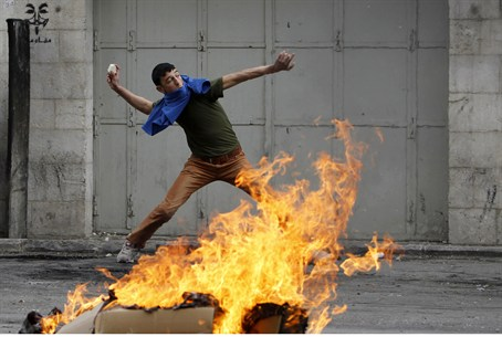 Protester throws a rock during clashes with I