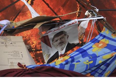 A poster of Morsi burns after police clear pr