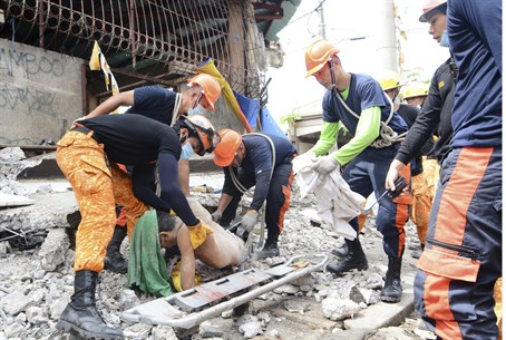 Rescue workers pull a body from the rubble fo