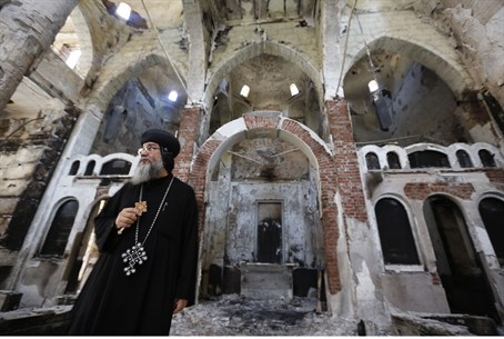 Coptic priest surveys damage to church wrough
