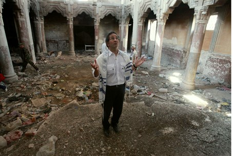 Jewish refugee David Gerbi prays in a ruined