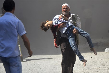 Syrian man carries wounded boy