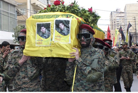 Hezbollah members carry the coffin of a fight