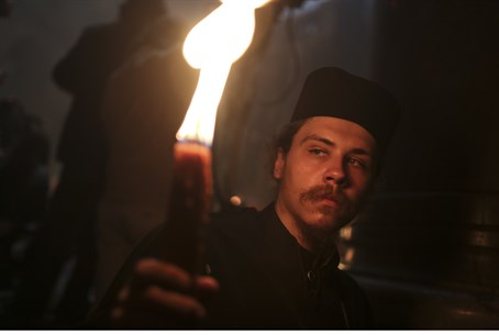 Orthodox Christian pilgrim holds a candle dur