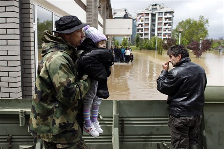 Serbian soldier evacuates child from flooding