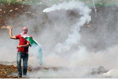 Arab rioter lobs tear gas on 'Nakba Day'
