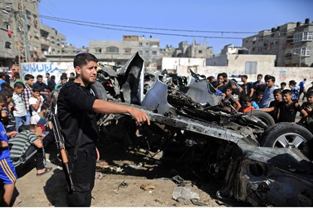Palestinians gather round wreckage of car tar