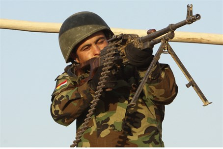 A member of Kurdish Peshmerga forces takes ai