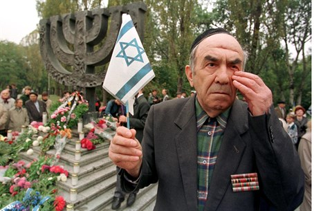 A Babi Yar survivor wipes a tear at a memoria