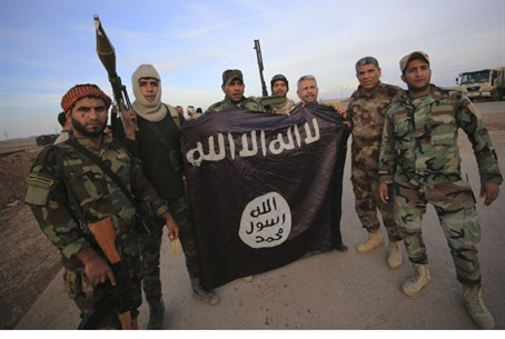 Iraqi Shi'ite fighters pose with captured ISIS flag (file)