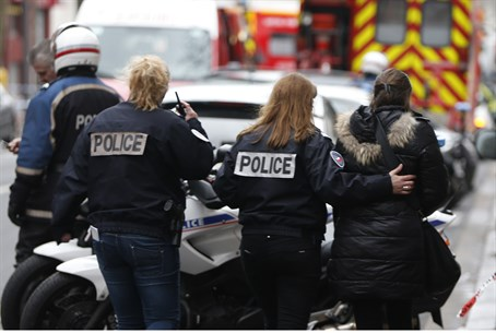 French police assist a woman following Cherlie Hebdo shooting attack