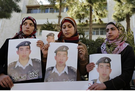 Relatives of captive Jordanian pilot Maaz al-Kassasbeh, including his wife (C), hold poste