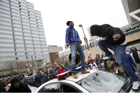 Justified anger? Rioters destroy a pollice car in Baltimore
