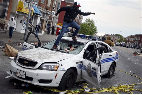 Rioters destroy a police car in Baltimore
