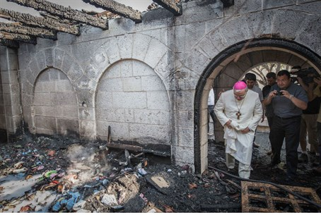 A priest inspects the damage at the Church of the Multiplication at Tabgha, on the Sea of