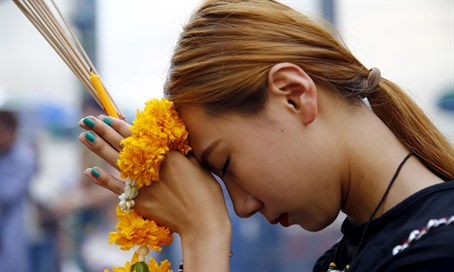 Woman prays at the Erawan Shrine in Bangkok following attack