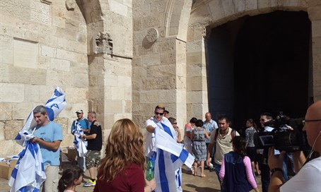 Im Tirzu activists give out flags outside the Jaffa Gate