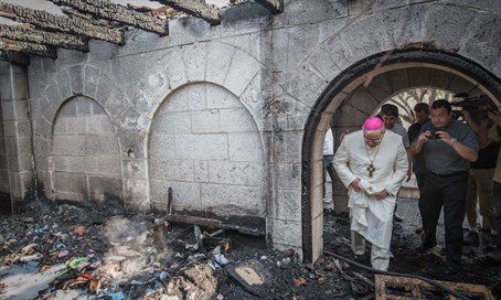 A priest inspects damage at Church of the Multiplication