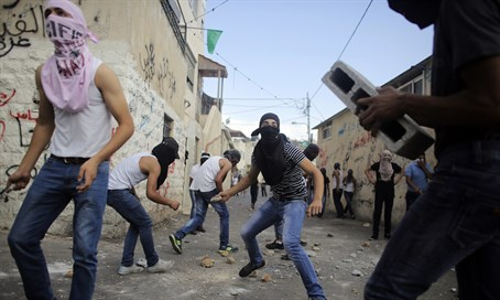Palestinians hurl stones during clashes with Israeli police in the East Jerusalem